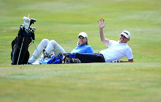 CHESTER, ENGLAND - AUGUST 12:  Gary Hendley of Stepaside Golf Centre(r) and Ben Daniels of Bletchingley GC has a rest during slow play on day one of the Golfbreaks.com PGA Fourball Championship Final at De Vere Carden Park Hotel on August 12, 2015 in Chester, England.  (Photo by Jan Kruger/Getty Images)